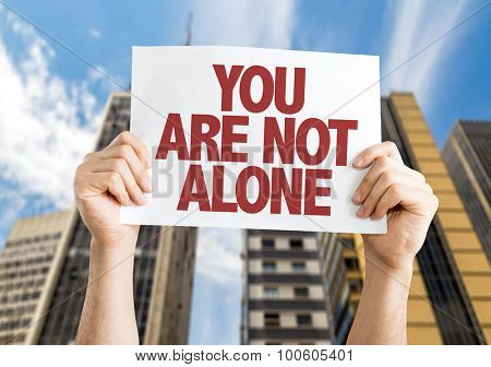 You Are Not Alone placard with cityscape background