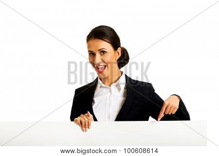 Happy businesswoman pointing on white banner.