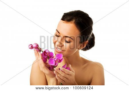 Woman with purple orchid branch and closed eyes