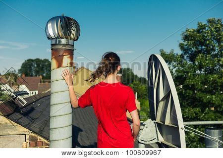 Young Woman Standing On Roof By Chimney