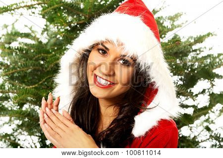 Beautiful santa woman with christmas tree on a background.