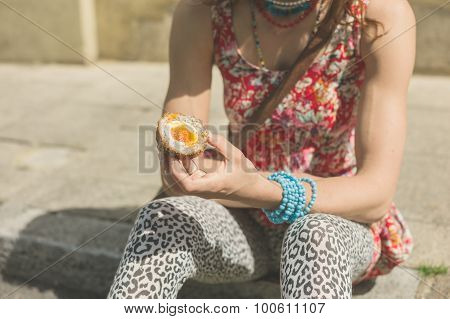 Young Woman Eating Scotch Egg In The Street