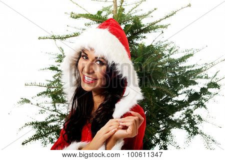 Santa woman with christmas tree on background.