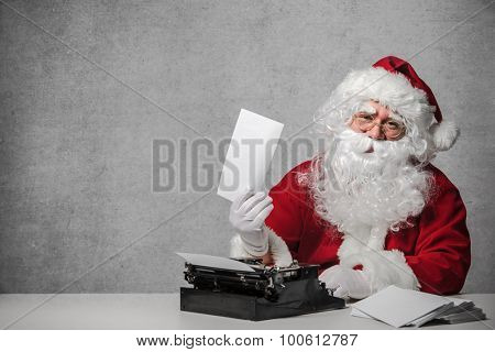 Santa Claus typing a letter on an old typewriter