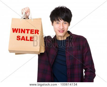 Happy Asian man shopper holding shopping bag for showing phrase of winter sale