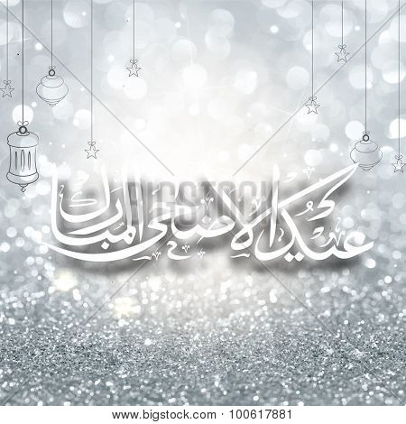 Arabic Islamic calligraphy of text Eid-Ul-Adha Mubarak on shiny silver glitter background for Muslim community Festival of Sacrifice celebration.