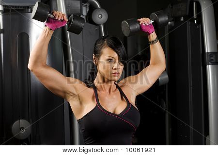 Asian Woman Concentrating While Working Out With Weights
