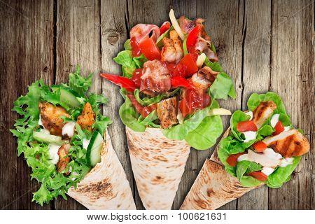 Tortilla chicken wrap sandwich on wooden background.