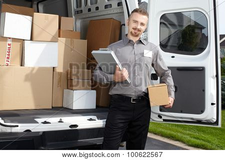 Young postman with parcel near delivery truck. Shipping service.