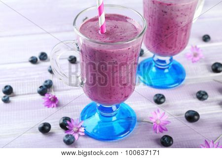Glasses of blueberry smoothie on wooden table, closeup