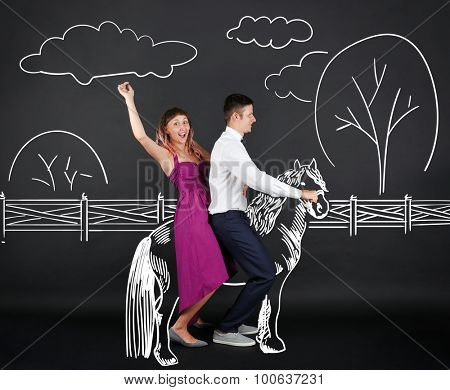 Funny young couple on horse, on black background