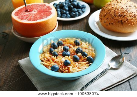 Tasty cornflakes with fruits and berries on table close up