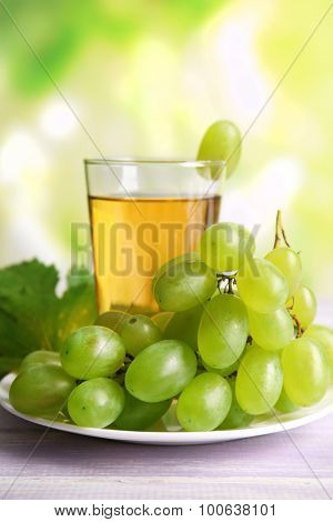 Glass of grape juice on wooden table on light blurred background