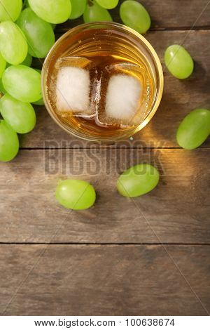 Glass of grape juice with ice cubes on wooden table, closeup