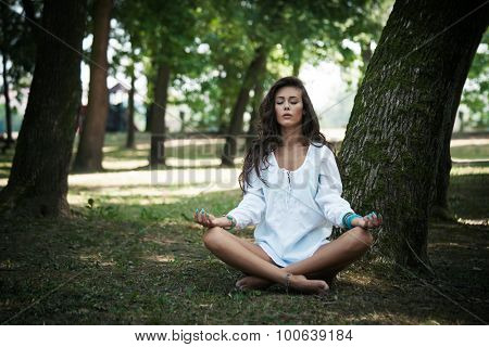young barefoot woman in white shirt practicing yoga in  park, full body shot, natural light