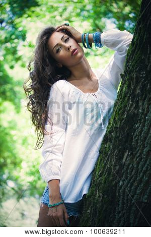 young woman in simple white shirt and blue jeans shorts lean on tree, day shot, natural light, look at camera