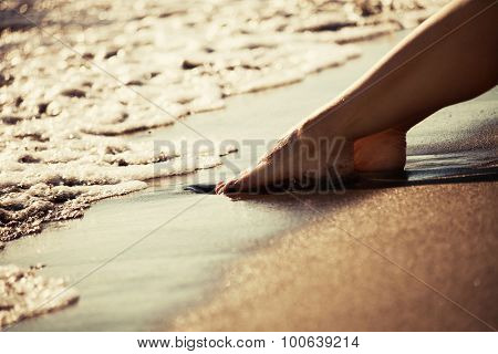 woman barefoot legs on sand beach by the sea at sunset, closeup,  selective focus, gold color