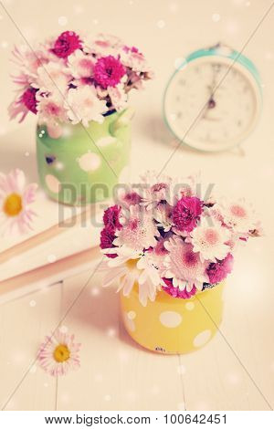 Beautiful flowers in polka dot vases on table