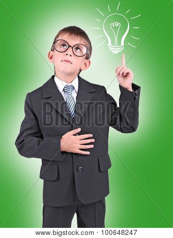 Little schoolboy with idea bulb above the head on green background