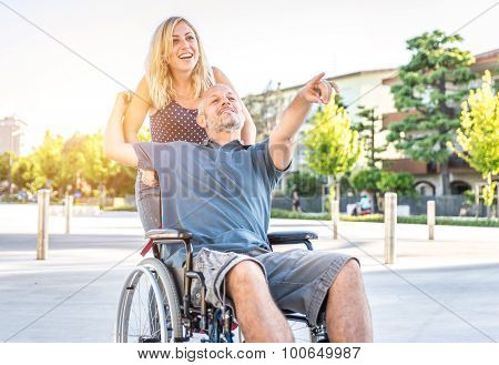 Couple In Love In The City Center. Man With Desease On A Wheelchair And His Lovely Woman