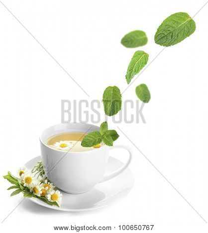 Mint leaves falling in cup of herbal tea, isolated on white