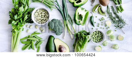 Healthy spread of green vegetables on rustic white background from overhead, broccoli, celery, avocado, brussel sprouts, kiwi, pepper, peas, beans, lettuce,