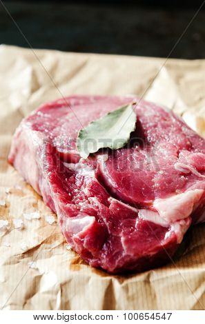 Raw ribeye steak on butchers paper with dried herb and coarse salt, graded in dramatic colour tone