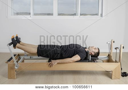 Man Doing Pilates In Reformer Bed.