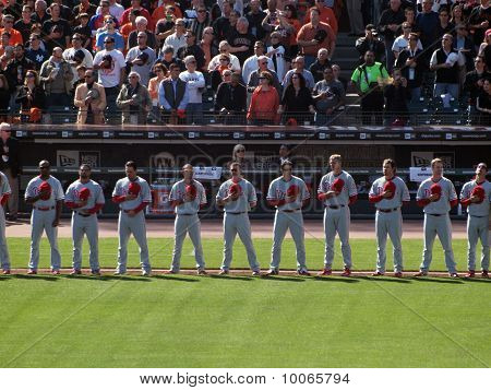 Phillies Players Stand In A Line With Hats Removed During National Anthem