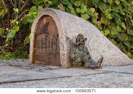 Dwarf guards the entrance of a small building