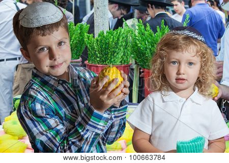 The Jewish holiday of Sukkot. Cute little boy with long blond hair in  knitted skullcap and  seven year old boy in white skullcap with etrog. They stand  on a pre-holiday market in Jerusalem.