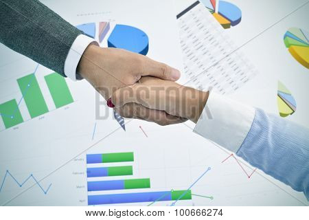 closeup of a businessman and a businesswoman shaking hands above an office desk full of charts