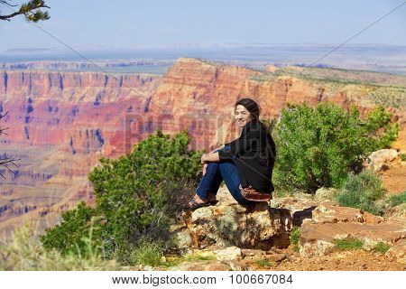 Biracial Teen Girl Sitting Along Rock Ledge At Grand Canyon
