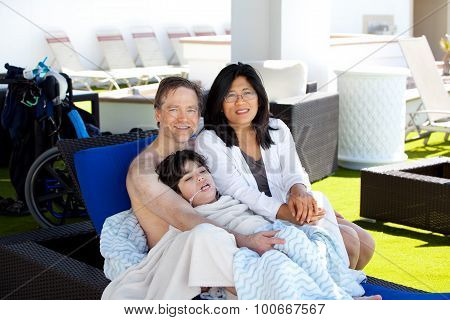 Father And Mother With Disabled Son On Blue Lounger Off Side Of Pool, Under Cabana