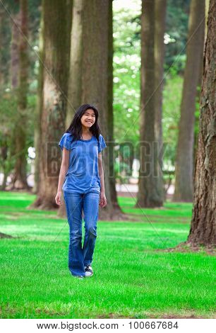 Young Teen Biracial Girl Walking Under Tall Trees