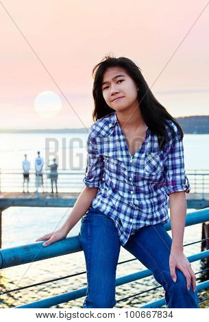 Young Teen Biracial Asian Girl Sitting On Metal Railing By Lake At Sunset