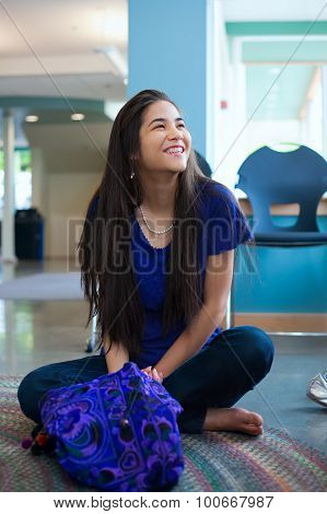 Beautiful Biracial Teen Girl Sitting Crossed Legged On Floor Smiling, Looking Up To The Side