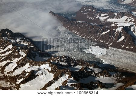 Aerial view of a glacier front and mountains in Greenland