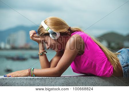 Young girl posing on the pier listening to music