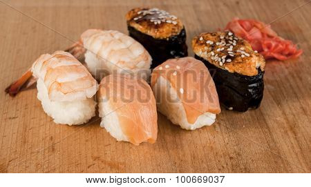 Delicious fresh Japanese sushi rolls . Set with salmon, eel , cheese, california, flying fish roe , red caviar , wasabi mustard Imber . On a wooden board. Great photos for newspapers, magazines.