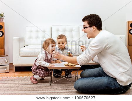 A young father feeding two little children - a boy and a girl at home.
