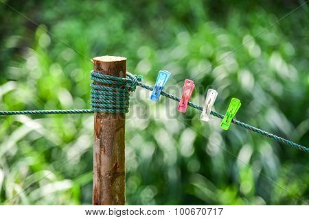 Colorful Of Clothespin Clamp On Rope With The Green Nature Background