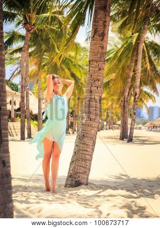 Blonde Girl In Azure With Hands On Head Among Palms On Beach