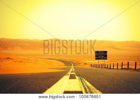 Winding black asphalt road through the sand dunes of Liwa oasis United Arab Emirates