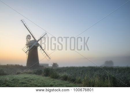 Windmill In Stunning Landscape On Beautiful Summer Dawn