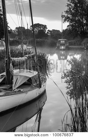 Boats Moored On Riverbank At Sunrise In Countryside Landscape In Black And White