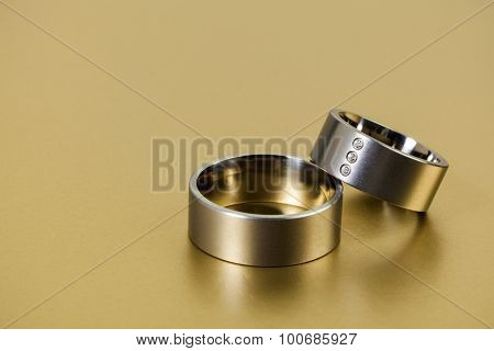 Pair of platinum wedding rings on golden background with copy space
