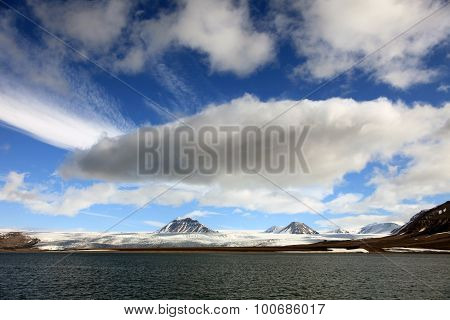 Puffy white clouds blue sky mountain peaks and glaciers in Svalbard Norway
