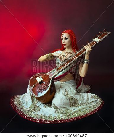 Beautiful Redhead Woman In Indian Sari With Oriental Jewelry Playing The Sitar