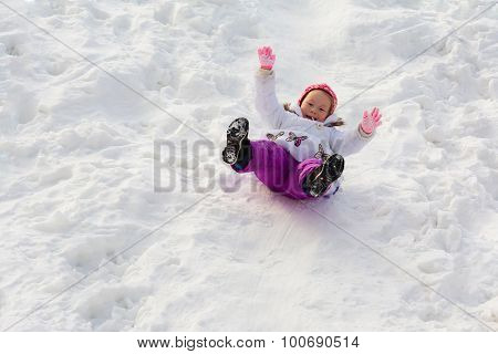 The little girl slides sitting on an ice slope